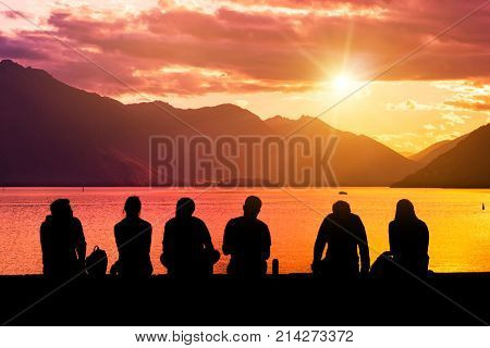 Silhouette Group Of Young People Sitting On Beach