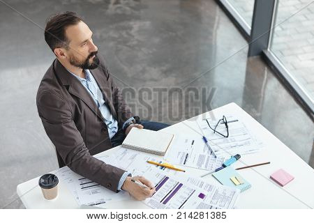 Top View Of Serious Male Manager Dressed Formally, Works In His Cabinet, Studies Documents For Makin