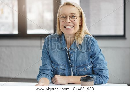 Stylish Female Designer Sits At Work Place With Takeaway Coffee, Waits For People To Present Her Blu
