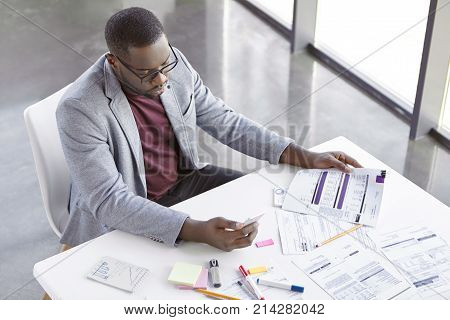 Portrait Of Successful Prosperus Dark Skinned Male Works With Documents, Searches Important Informat