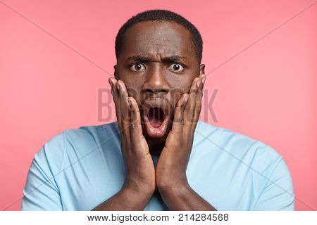 Surprised Stunned Stupefied Black Man Realizes Bad News, Keeps Hands On Cheeks, Being Amazed And In