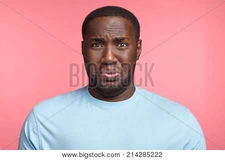 Portrait Of Discontent Sorrorful Black Man Has Gloomy Miserable Expression, Unhappy To Hear About Hi