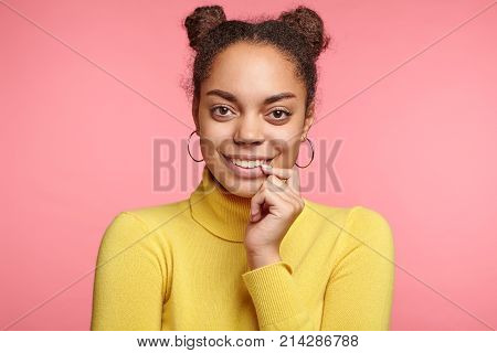 Portrait Of Happy Attractive Dark Skinned Woman With Two Hair Buns, Wears Yellow Polo Neck Sweater,