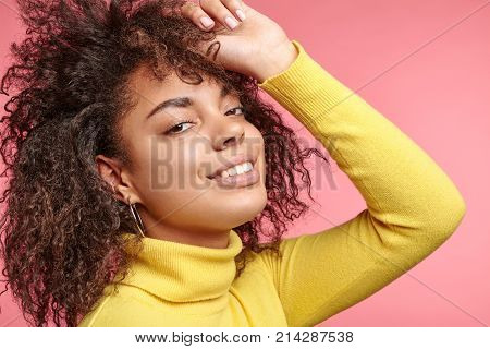 Close Up Of Fashionable Confident Pleasant Looking Afro Woman Has Curly Bushy Hair, Touches Head, St