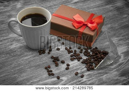 gift box, coffee beans and cup of cofee on gray wood background