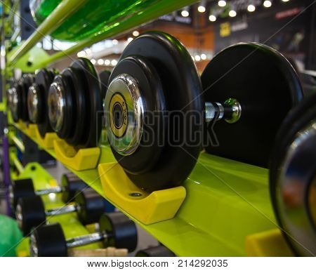 Dumbbells in gym close up many on rack in sport fitness centre. Compound dumbbells with black rubber wheels on counter of store
