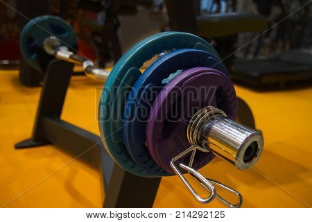 Sport equipment in gym. close-up view of a barbells on a stand in the sports hall with colored weight.