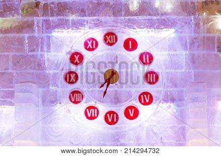 Ice clocks - original watch made of ice blocks with ligh bulbs. Outdoor decoration for Christmas and New Year celebration. Moscow Russia.