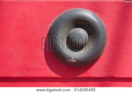 Grey metallic iron rivet on red wall background