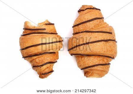 bitten croissant decorated with chocolate sauce isolated on white background, top view.