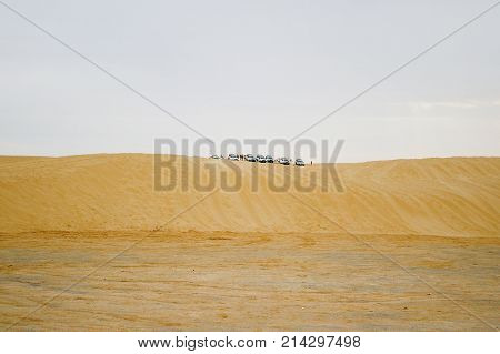 Group of off-roadster cars on sand hill. Car tour of the Sahara desert. Tunisia.