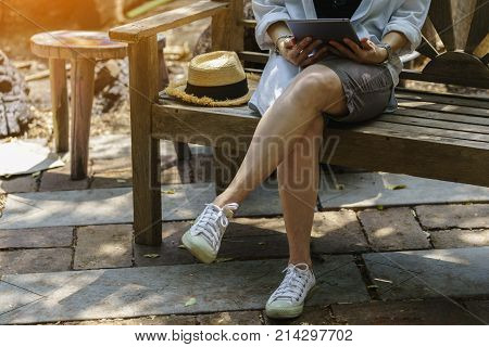Woman's hands holding tablet sitting on wooden chair in the garden