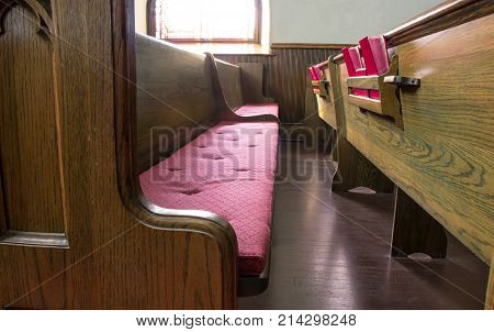 Empty Church Pew. Interior of an empty church with pew and row of bibles.