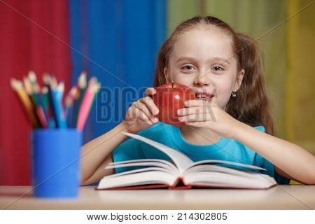 Portrait Of Happy Pretty Girl Holding A Red Apple In The Classroom