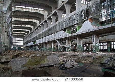 Old destroyed factory hall. Huge industrial space in a forgotten place. The wall of broken glass in the background.