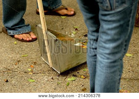 Metal trash tray with many cleaners wearing jeans