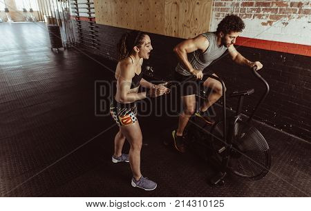 Fitness Trainer Motivating Man At Gym