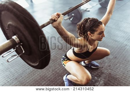 Fit female athlete exercising with heavy weights at cross training gym. Young woman doing deadlift with heavy barbells in gym.