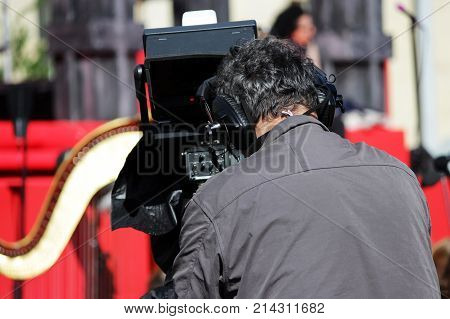 professional videographer shoots on video camera a concert with orchestral accompaniment in Gatchina, Leningrad Region Russia.