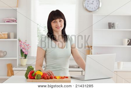 Lovely brunette woman relaxing with her laptop while standing in the kitchen