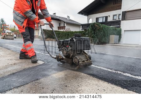 Worker with vibrating plate during asphalting work on sidewalk