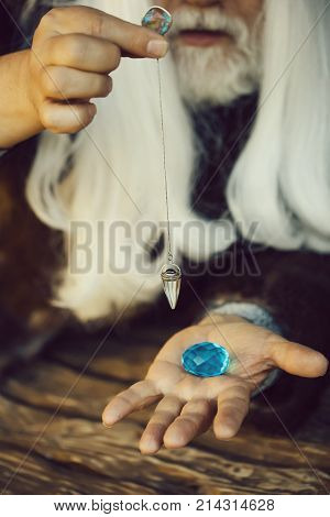 Old bearded man wizard with long white hair and beard holding blue gem stone and silver pendant for hypnosis on wooden background