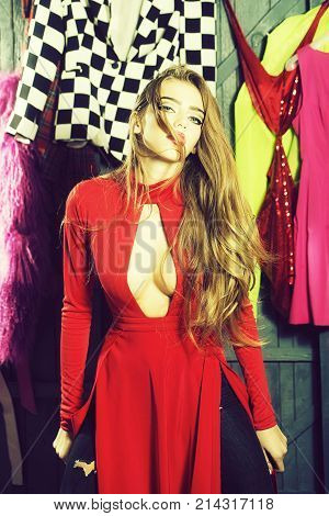 Portrait of one sexual pretty sensual diva young woman with long hair in red dress with deep low neck standing in wardrobe among many colorful bright clothes vertical picture