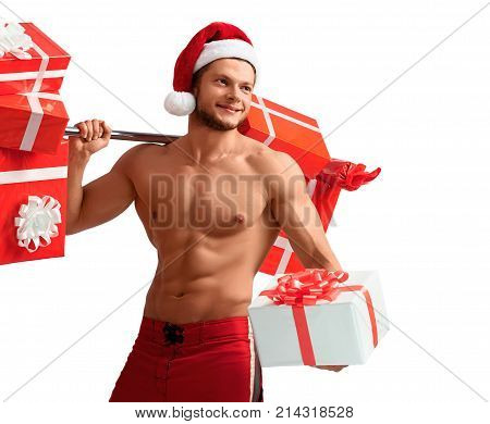 Fitness with Santa. Cropped halflenght studio shot of a young fitness trainer with muscular body wearing Santa Claus hat holding out a gift looking away smiling cheerfully. 2018, 2019.