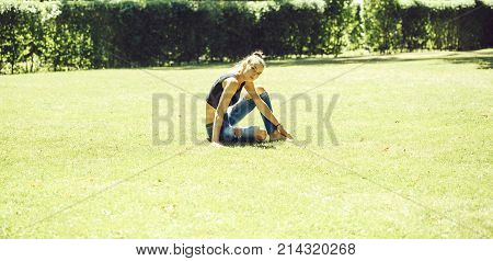 Pretty Girl Sits In Yoga Position On Grass