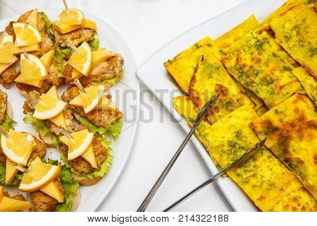 Two plates with snacks on a buffet table. Selection of tasty bruschetta or canapes on toasted baguette and quark cheese topped with fried meat or fish orange and green salad egg omelette with herbs. restaurant feed. New Year Christmas