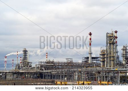 general view of a chemical or oil refinery with a multitude of pipelines factory pipes and distillation columns under a cloudy sky