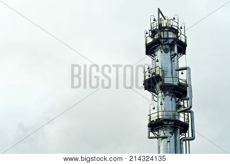 the upper part of a shiny gigantic metal fractionating column at a chemical or refinery with a sky background