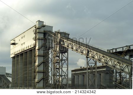 fragment of a modern industrial enterprise with silos for storage of loose materials and an inclined covered belt conveyor