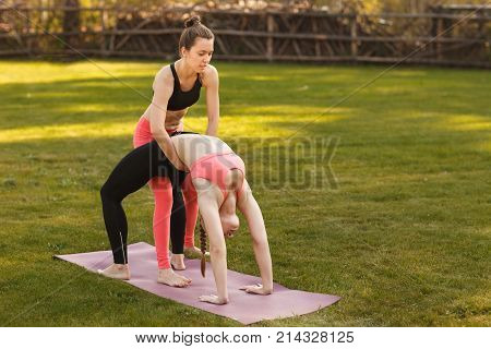 Yoga Instructor Helps Beginner To Make Asana Exercises Outdoor.