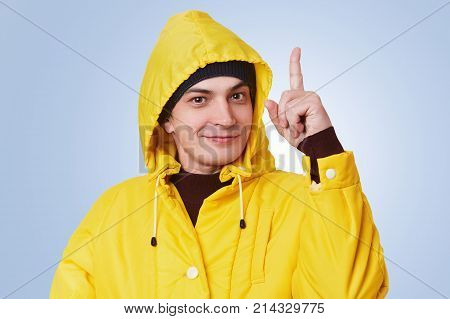 Clever Handsome Man Raises Fore Finger As Gets Brilliant Idea, Wears Yellow Raincoat, Has Happy Chee