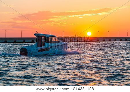 The setting sun over the sea and the motorboat sailing along the mole