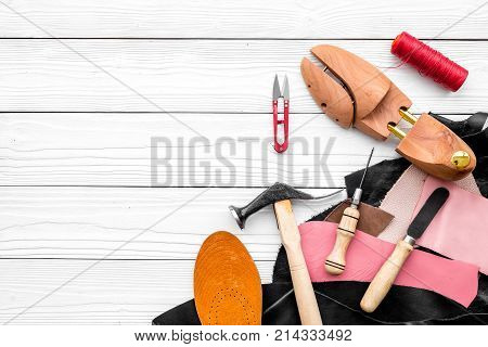 Shoemakers' craft. Tools, wooden last, pieces of leather on white wooden background top view.