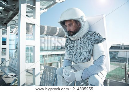 Boring spending time. Thoughtful cosmonaut is sitting on bench and looking forward with pensive sight. Waist up portrait. Copy space on left side