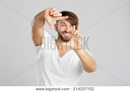 Cheerful handsome bearded man posing at studio smiling happily making frame with his fingers grey background positivity lifestyle youth hipster stylish masculine leisure focusing sign shape.