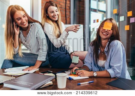 Two girls laughing at their friend with a sticky note on her face. Group of female students relaxing having fun in classroom during a break.