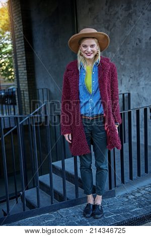 Full length portrait of excited young woman standing near underground crossing and laughing. She is wearing styled coat and hat