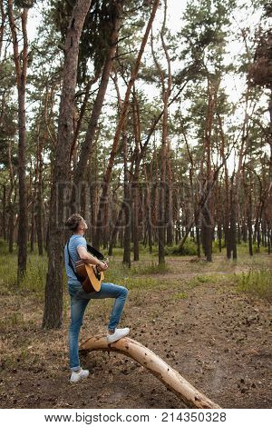 Talented guitarist playing forest hiking concept. Lifestyle of the artist. Unity with the nature.