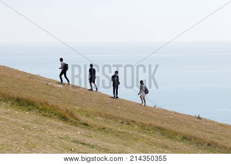 SUSSEX GREAT BRITAIN - JUN 18 2017: Silhouette of people climbing the white chalk cliffs in the Seven Sisters Country Park. June 18 2017 in Sussex Great Britain