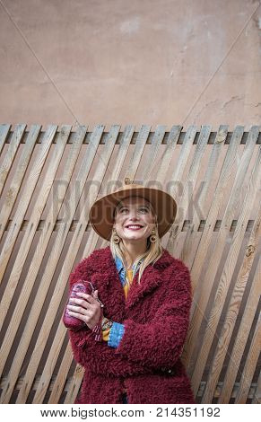 Waist up portrait of excited young woman standing near wooden palisade and looking up with joy. She is keeping small clutch bag and smiling. Copy space above