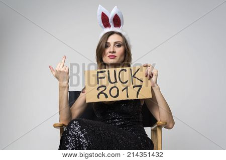 A young haughty girl in black dress and Christmas rim with hare ears with a sign