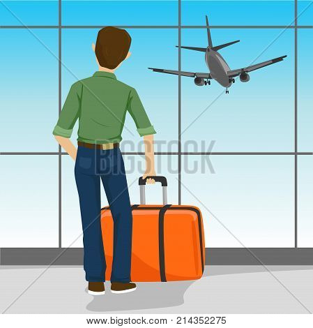 Rear view of man standing with a suitcase in airport watching landing aircraft