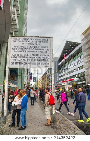 BERLIN - AUGUST 21 2017: Historical sign at Checkpoint Charlie on August 21 2017 in Berlin Germany. The name was given by the Western Allies to the best-known Berlin Wall crossing point between East and West Berlin.