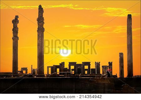 Persepolis is the capital of the ancient Achaemenid kingdom. Ancient columns. Sight of Iran. Ancient Persia. Orange sunset background. Artistic image.