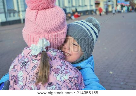 The boy hugs the girl and smiles and is happy. Brother hugging sister loves her. On the face emotions and feelings. Pulls her to him. The boy's blue eyes. They make friends and walk on the street.