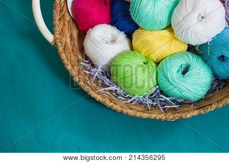 Colourful yarn balls in the basket on the wooden background. Toned.